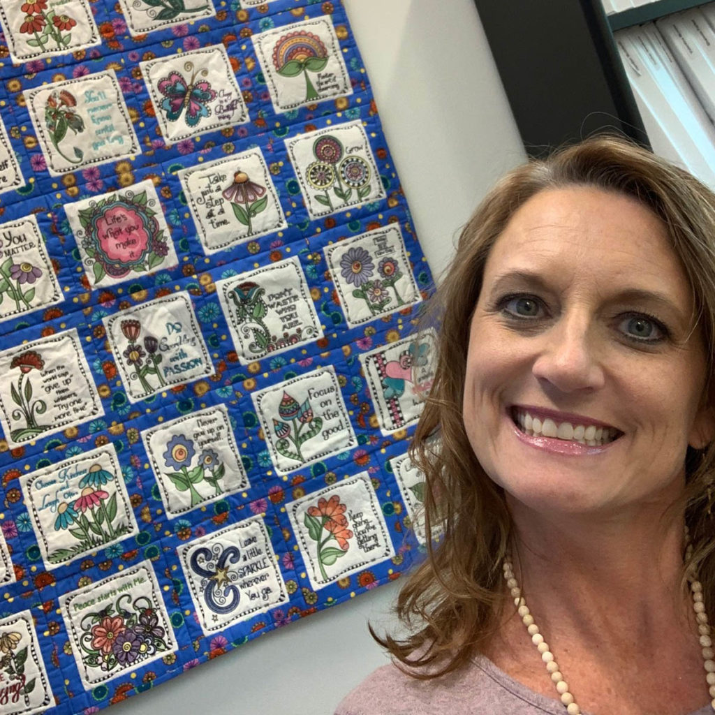 Image of Marsha Creter with her inspirational quilt that she made from Debi Payne Designs inspirational machine embroidered patterns